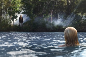 "Chelsea (Willa Ford) discovers Jason (Derek Mears) watching her from the shores of Crystal Lake in the 2009 remake of ""Friday the 13th."""